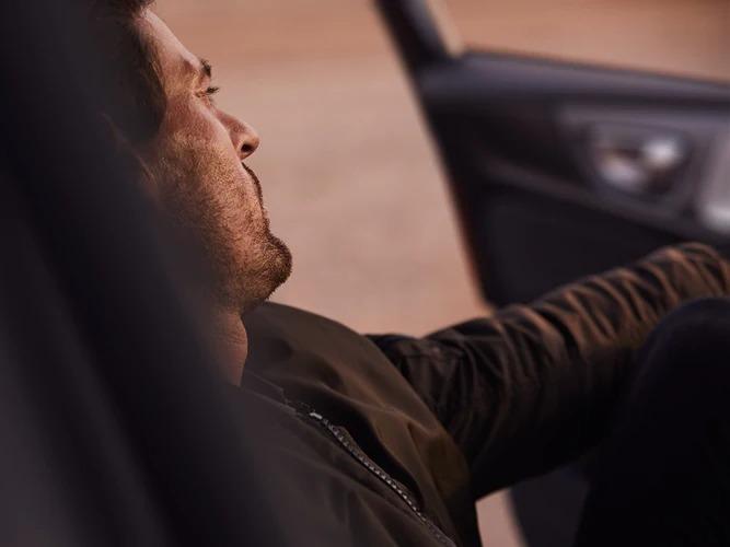 볼보 S60 안에 앉아 얼굴에 햇살을 받고 있는 갈색 머리 남성