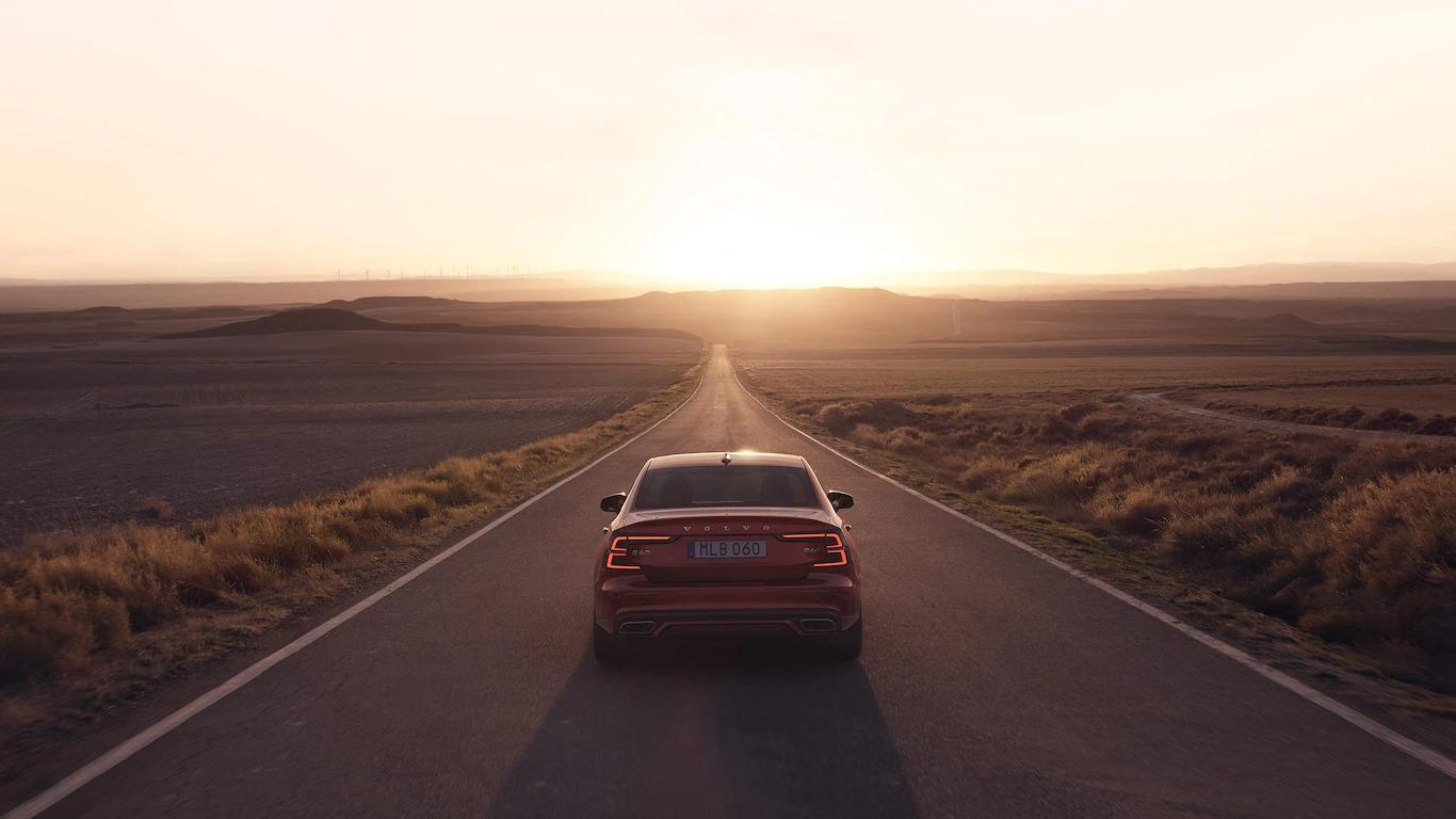석양 아래 도로를 주행하는 빨간색 볼보 S60.