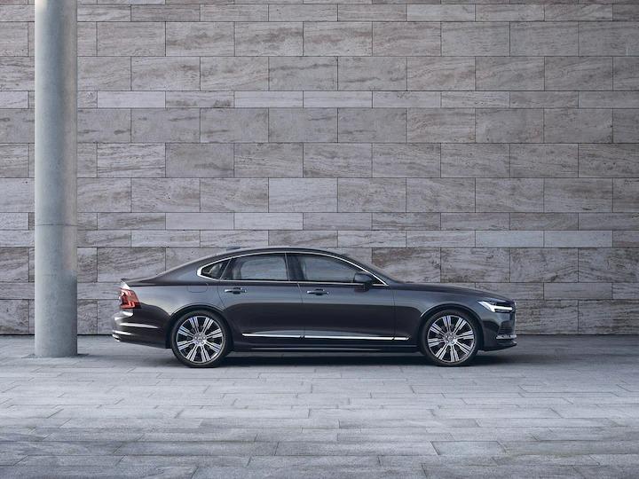 회색 벽 앞에 주차된 다크 Volvo S90