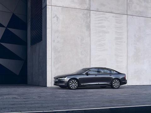 회색 벽 앞에 주차된 어두운 색상의 볼보 S90.