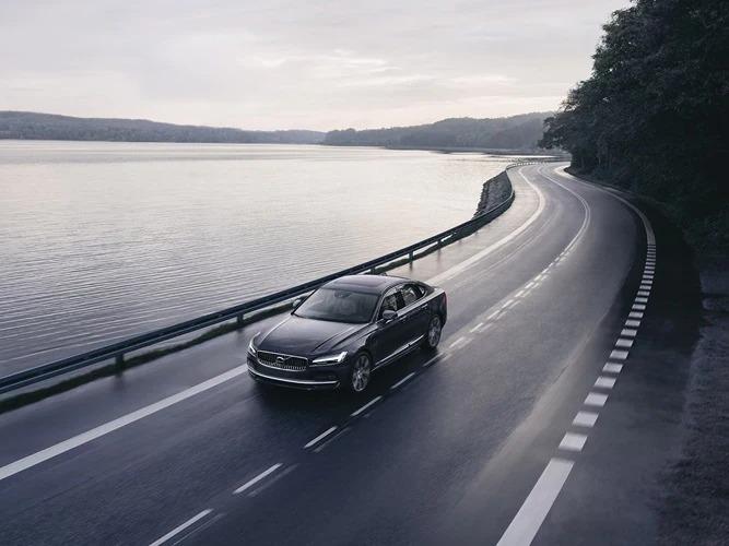 호수 옆 도로를 주행하는 Volvo S90 Recharge