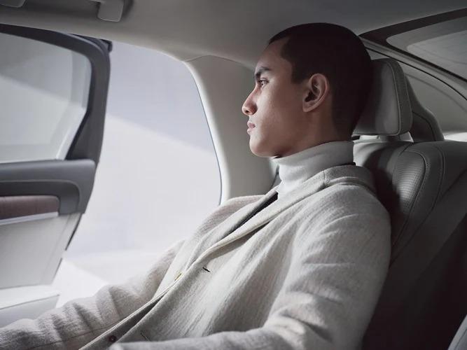 Volvo S90 Recharge 뒷좌석에 앉은 남성이 바깥을 바라보고 있고 문이 열려 있는 모습