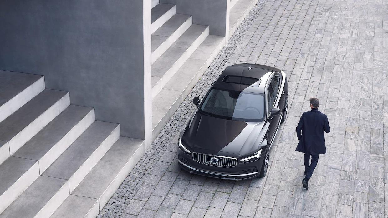 계단 세트 앞에 위치한 Volvo S90 앞으로 남성이 걸어가는 모습