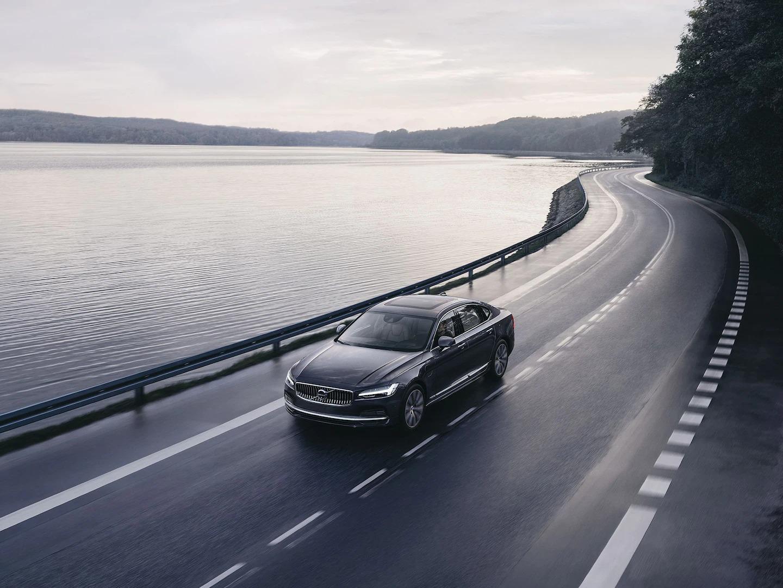 볼보 S90 마일드 하이브리드가 해안가 도로를 주행하고 있습니다.