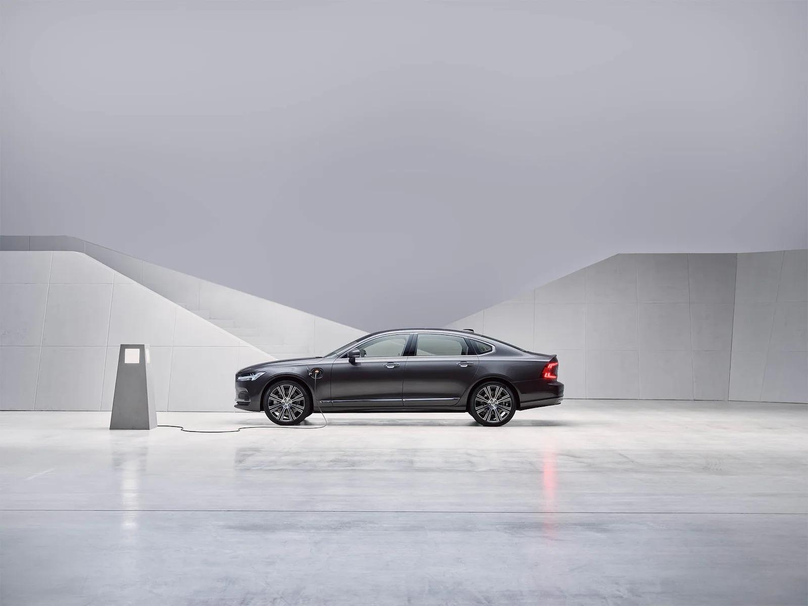 페블 그레이 Volvo S90 플러그인 하이브리드 세단이 정차된 채로 충전되는 모습