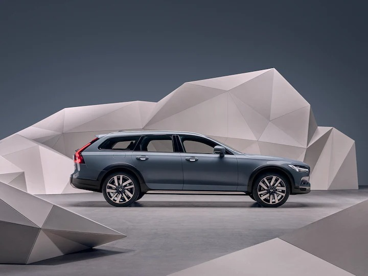 예술적인 느낌의 벽 앞에 서 있는 머슬 블루 메탈릭 Volvo Estate V90