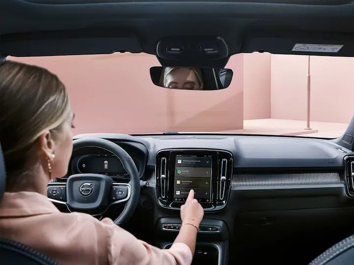 볼보 XC40 Recharge 차량 안에 있는 여성이 커넥티비티 시스템을 사용하는 모습