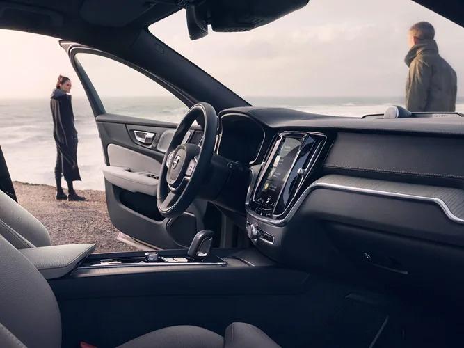 해변을 따라 서 있는 여성, 한쪽 문이 열린 Volvo V60 크로스 컨트리