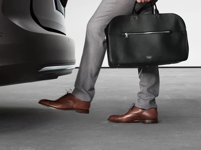 갈색 신발을 신은 남성이 후방 범퍼 밑으로 발을 움직여 트렁크 문을 엽니다