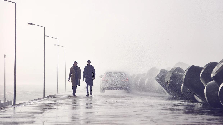 비를 뚫고 지나가는 V60 크로스 컨트리와 부두를 걷는 두 남성.