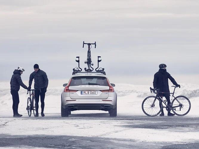 눈 내리는 풍경 속, 산악 자전거를 루프에 장착한 볼보 V60 크로스 컨트리.
