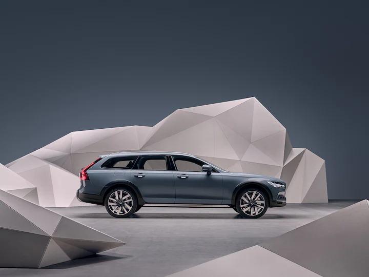 예술적인 느낌의 벽 앞에 서 있는 머슬 블루 메탈릭 Volvo V90 크로스 컨트리