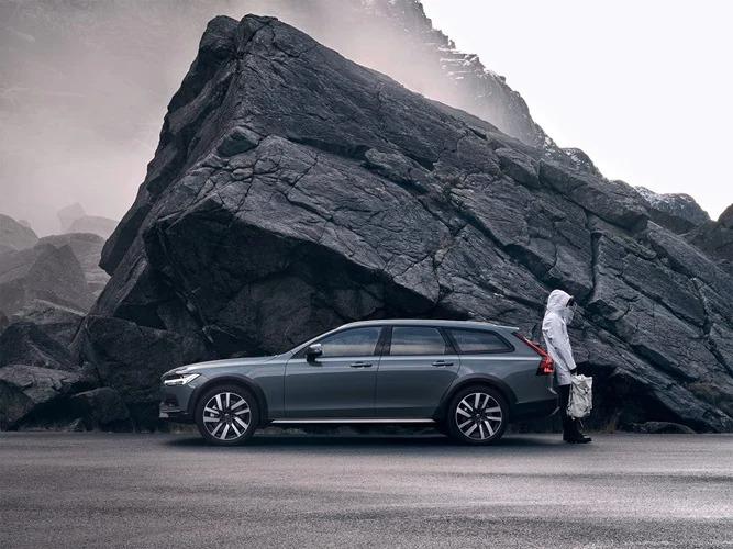 머슬 블루 V90 크로스 컨트리가 산 가까이 주차되어 있으며, 한 사람이 자동차에 기대 서 있습니다.