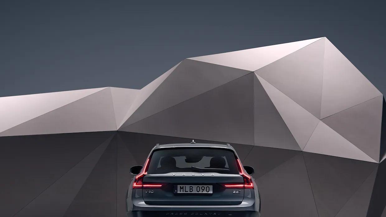 예술적인 느낌의 벽 앞에 서 있는 머슬 블루 메탈릭 V90 크로스 컨트리 후방 외관