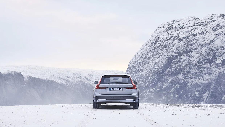 눈으로 덮인 산맥 길에 놓인 볼보 V90 크로스 컨트리 후면도.