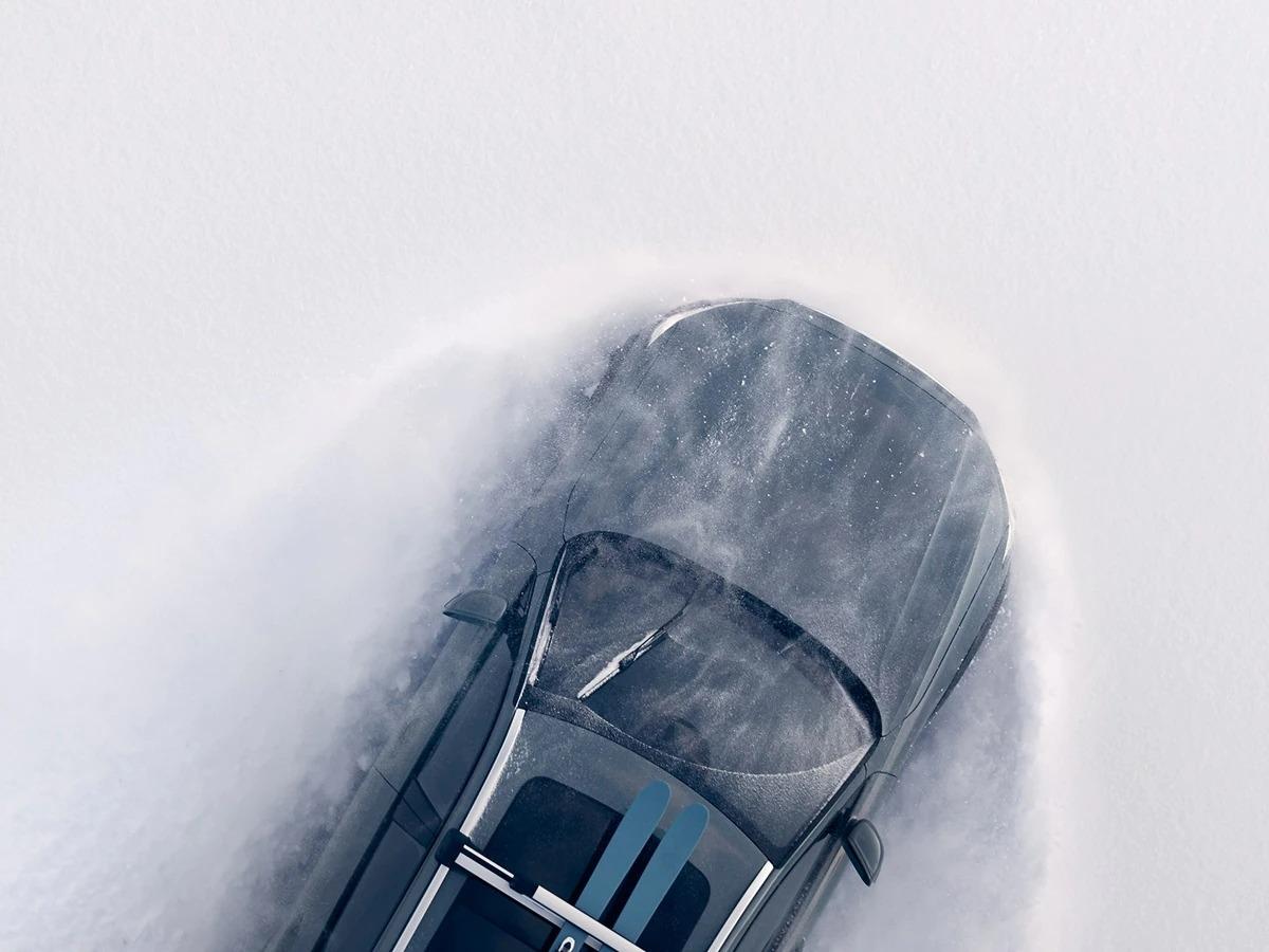 루프 위에 스키 세트를 싣고 폭설 속을 주행하는 머슬 블루 Volvo V90 크로스 컨트리