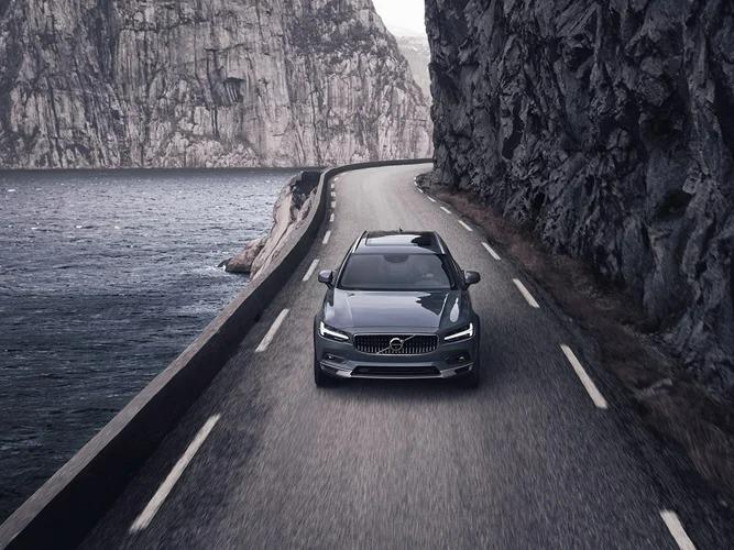 물과 산으로 둘러싸인 도로 위를 주행하는 머슬 블루 V90 크로스 컨트리