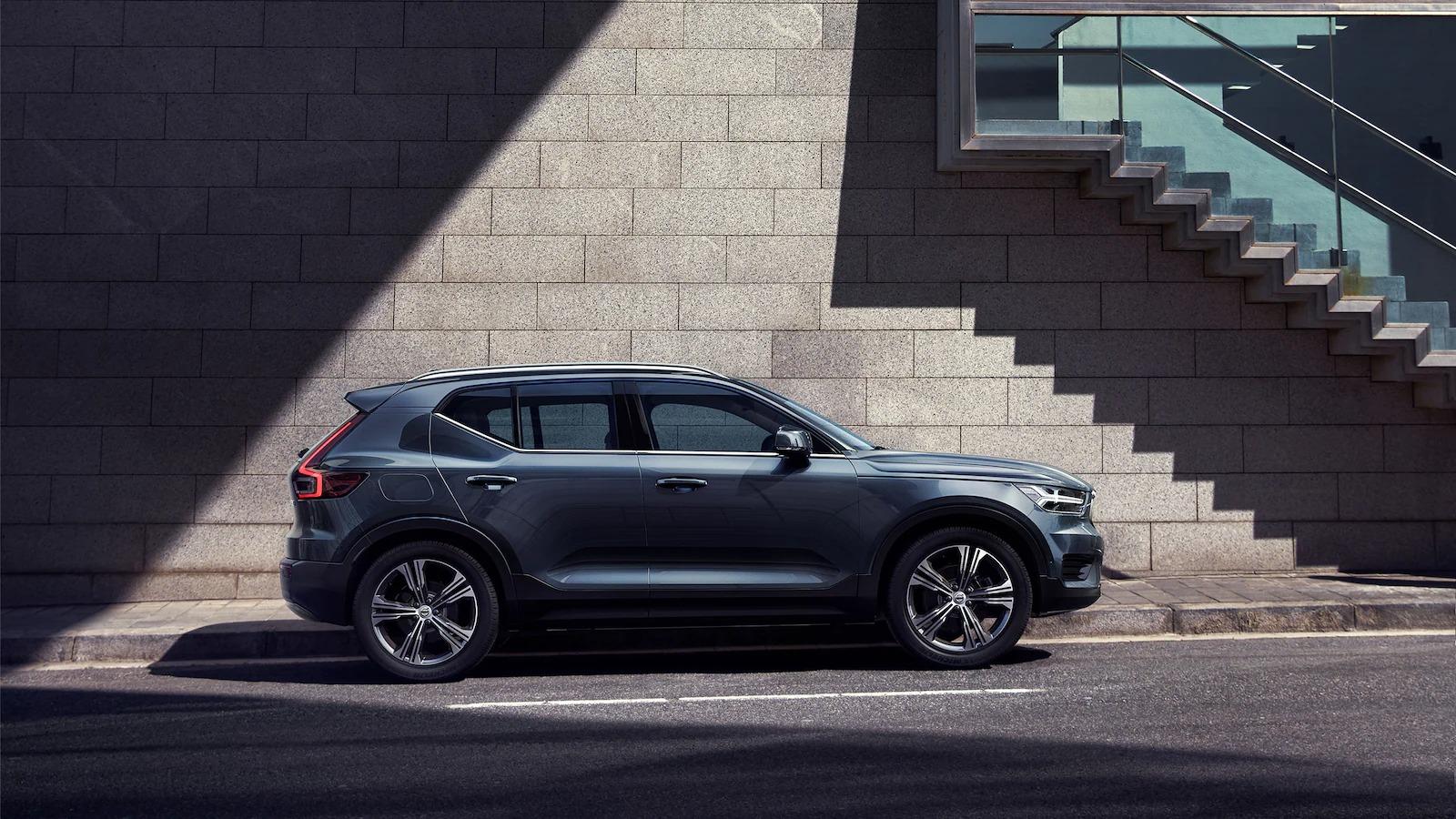 파란색 콘크리트 건물 정면에 남성이 기대어 서 있으며 그 옆으로 화이트 Volvo XC40가 있습니다