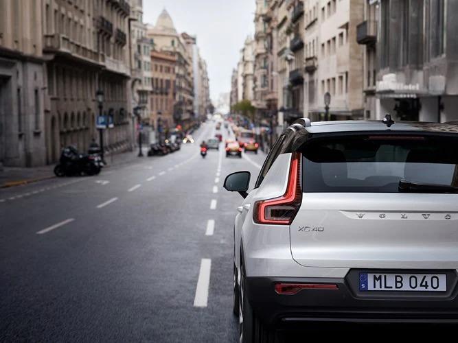 흰색 XC40 마일드 하이브리드가 도심 도로를 따라 주행하고 있습니다.