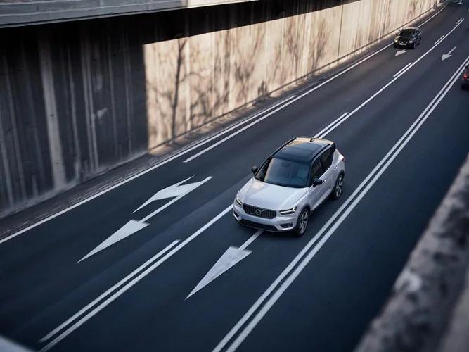 운전자 지원 기술을 통해 흰색 XC40이 다중 차선 도로를 주행하고 있습니다.