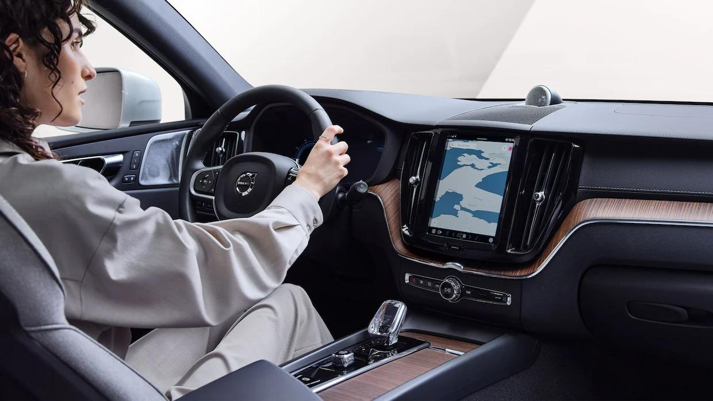 센터 콘솔에 지도 뷰가 있는 볼보 XC60 리차지를 운전하고 있는 여성의 모습을 보여주는 내부 전망입니다.