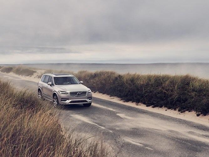 해안선을 따라 모래가 많은 작은 도로를 달리는 볼보 XC90.